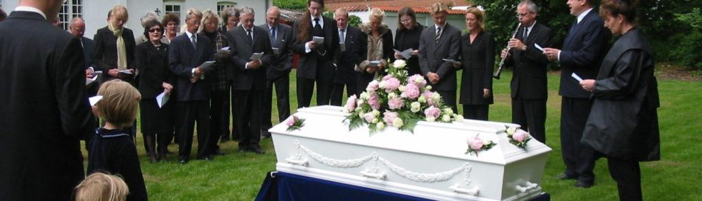 Mennesker synger ved begravelsesceremoni i have med blomster og hvid kiste